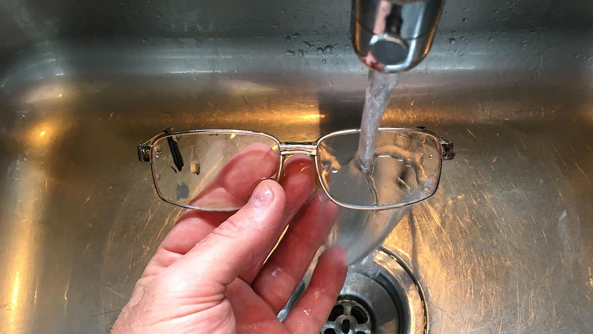 washing eyeglasses in the sink with alcohol-free eyeglass cleaner