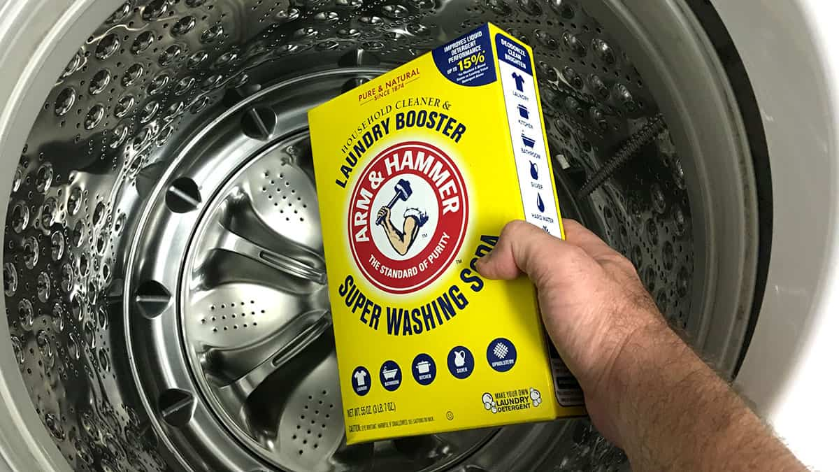 pouring Arm & Hammer Super Washing Soda into a washing machine