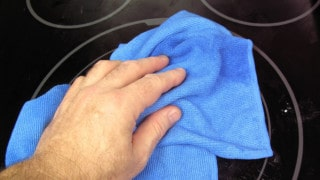 cleaning a glass-top stove with a Sollievo microfiber kitchen cloth