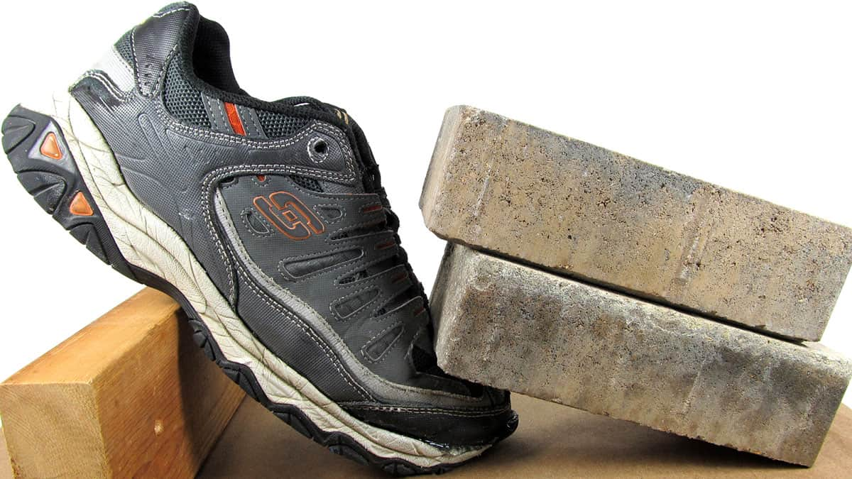 This is a running shoe in the process of being repaired with glue. The glued toe of the shoe is weighted down with bricks.