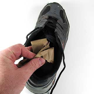 Stuffing paper in a shoe in preparation for sole gluing.